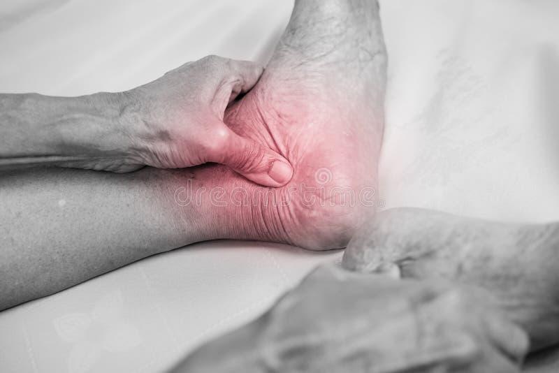 Tenencia de la mano del hombre mayor él pie y tobillo sanos del masaje en p imágenes de archivo libres de regalías