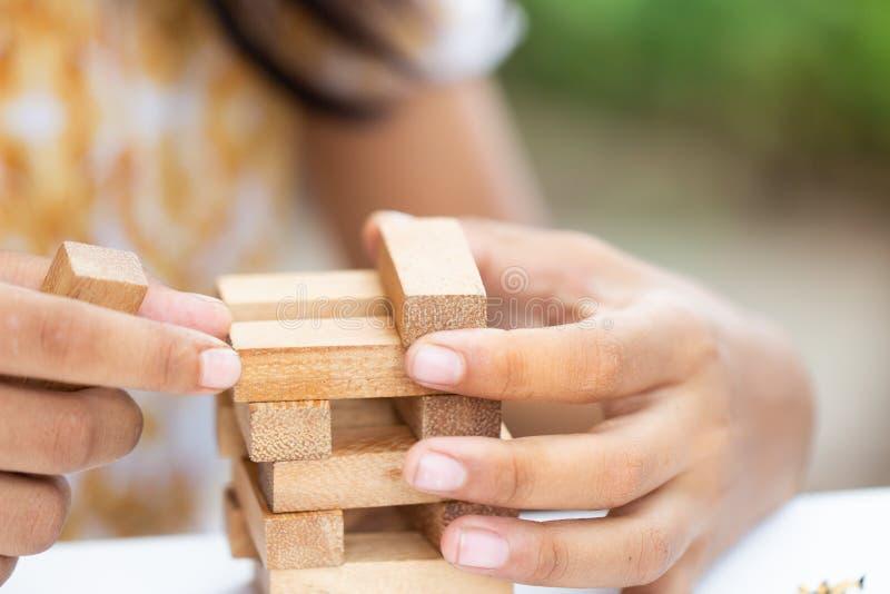 Tenencia de la mano de la muchacha que juega el bloque de madera, imagen de archivo