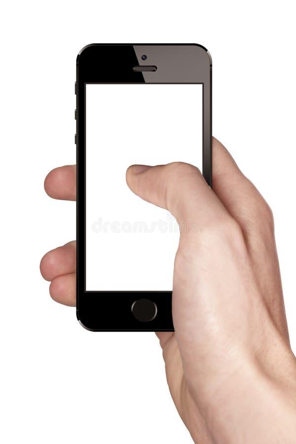 Tenencia de la mano y usar un iphone 5s foto de archivo libre de regalías