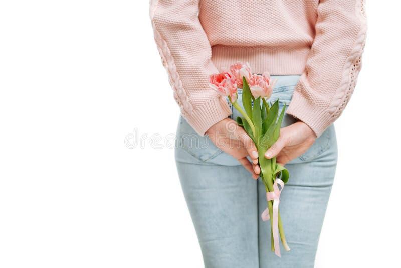 Tenencia de la mujer joven de tulipanes rosados detrás de su parte posterior en un fondo blanco fotos de archivo libres de regalías
