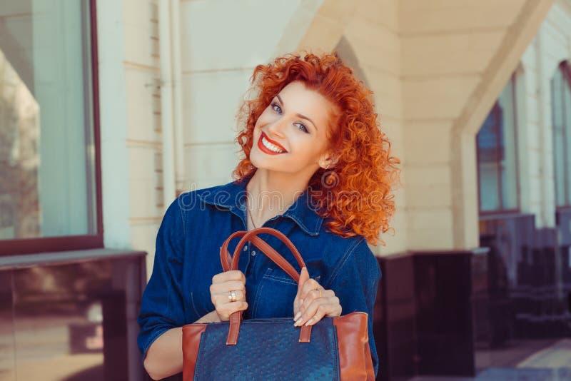 Tenencia de la mujer que muestra su nuevo bolso de cuero anaranjado de los vaqueros imagenes de archivo
