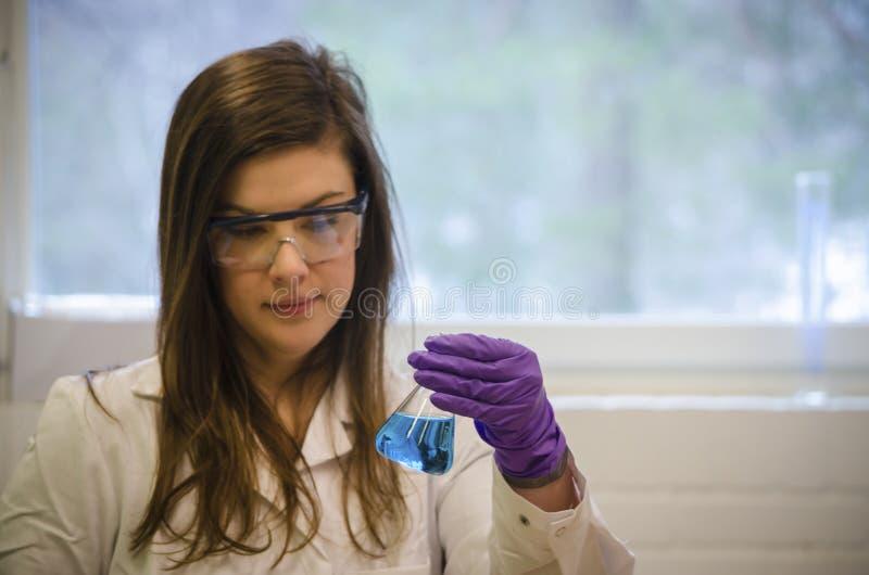 Tenencia del científico de la mujer y atención el pagar a una solución química azul en laboratorio de química fotos de archivo libres de regalías