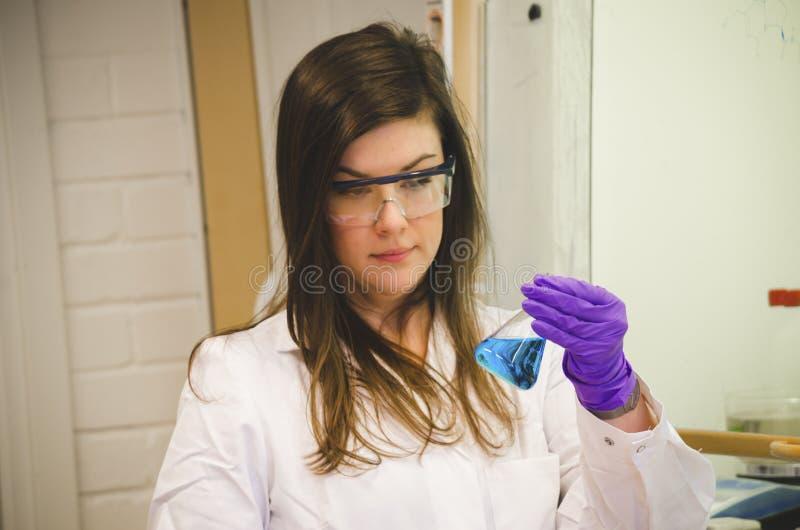 Tenencia del científico de la mujer y atención el pagar a una solución química azul en el laboratorio de química para la ciencia fotografía de archivo