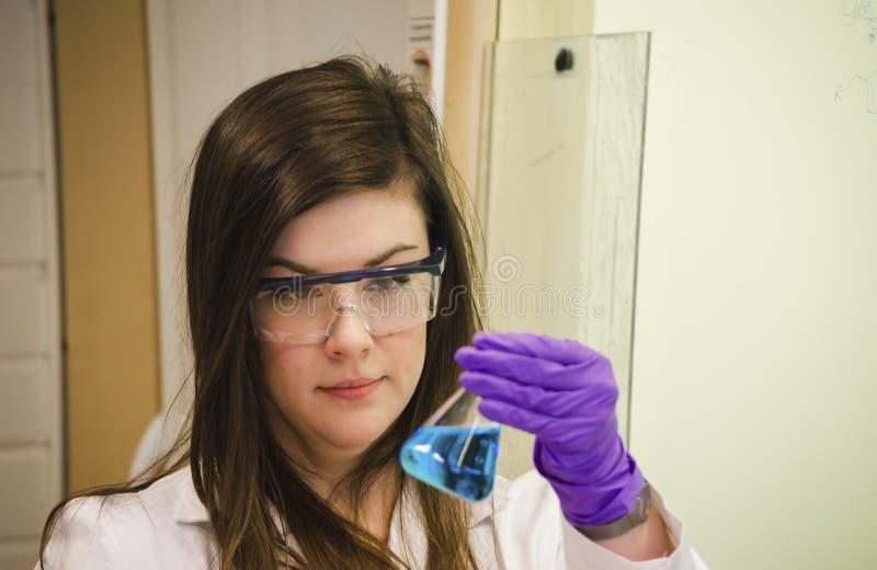 Tenencia del científico de la mujer y pagar cierre de la atención hasta una solución química azul en laboratorio de química fotos de archivo