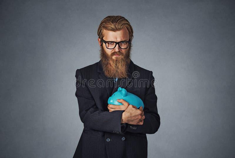 Tenencia del hombre con gesto de mano codicioso la hucha imagen de archivo libre de regalías