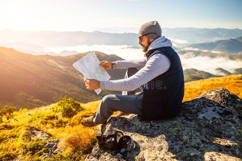 Tenencia del hombre joven del inconformista en manos y mirada en mapa en fondo de la montaña fotografía de archivo