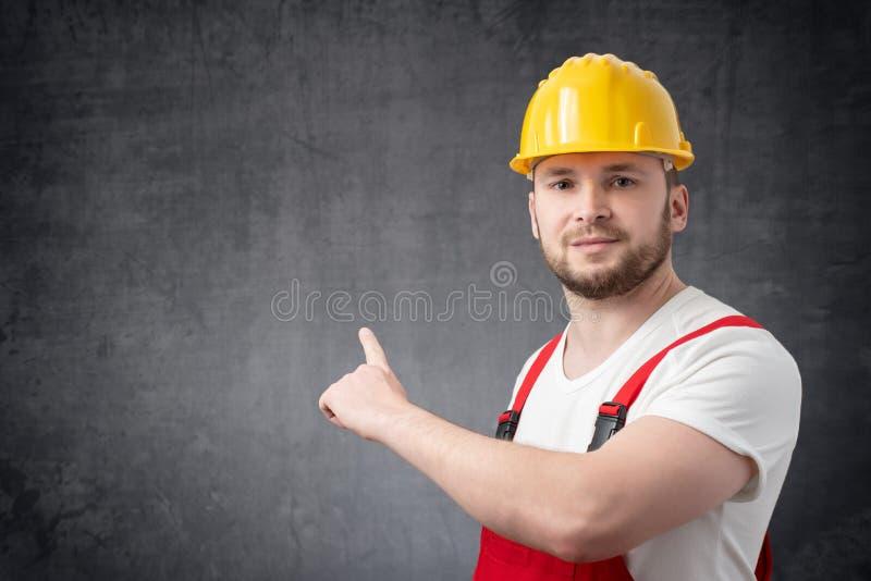 Tenencia del trabajador que señala en la pared fotos de archivo