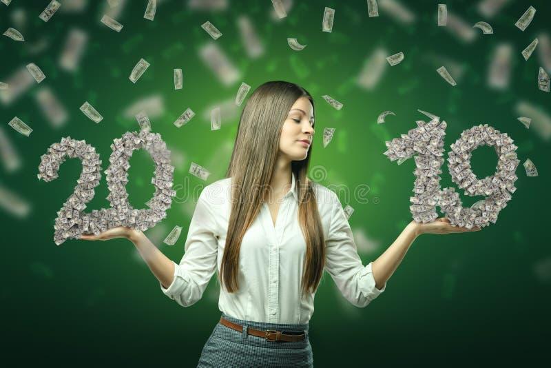 Tenencia joven '20' y '19' de la mujer de negocios muestras de dólar en sus manos con los dólares en el aire en fondo verde imagen de archivo libre de regalías