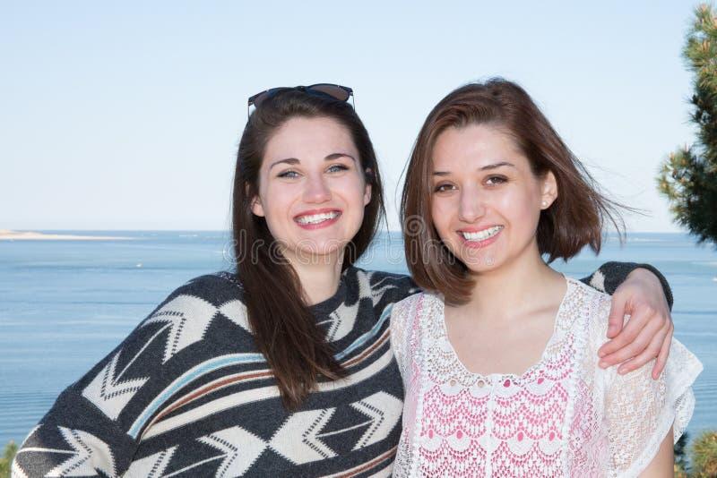 Tenencia lesbiana de los pares que se abraza en la costa de la playa foto de archivo libre de regalías