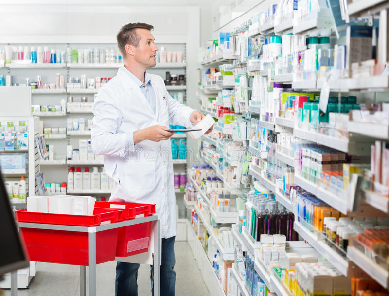Tenencia masculina de Counting Stock While del farmacéutico fotos de archivo libres de regalías