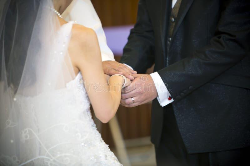 Tenendo le mani insieme nella cerimonia di nozze fotografia stock