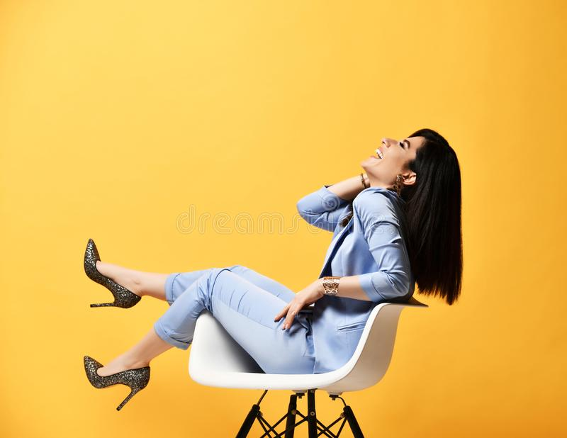 Tener morenita elegante de la mujer de negocios de la diversión en desgaste oficial se sienta en butaca del diseñador de lado y r fotografía de archivo