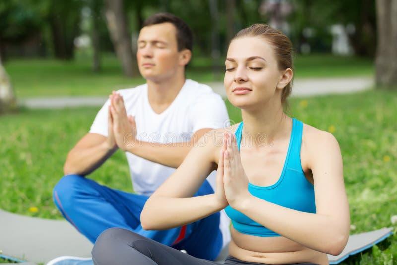 Tener práctica de la yoga en parque imágenes de archivo libres de regalías