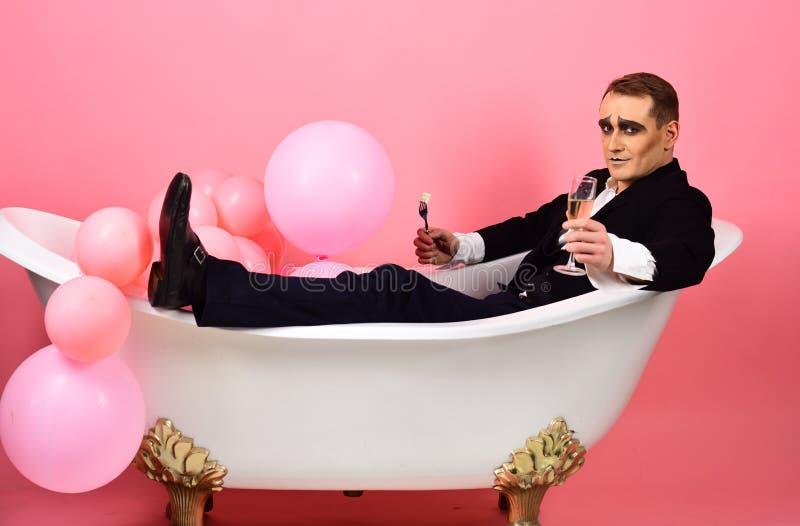 Tener un buen rato El actor del cómico celebra días de fiesta Imite al actor gozan el bañarse en tina de baño Imite al hombre tie imágenes de archivo libres de regalías