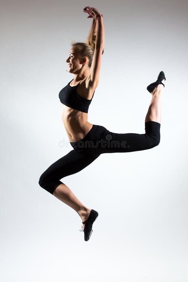 Tenerezza, tolleranza, melodia e plastica della ragazza relativa alla ginnastica Abbellisca il salto nell'aria della ragazza piac fotografie stock