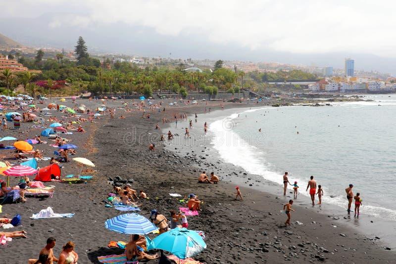 TENERIFE, SPAGNA - 2 GIUGNO 2019: Paesaggio urbano di Purto de la Cruz con la spiaggia con i bagnanti, Tenerife del nero di Playa immagine stock libera da diritti