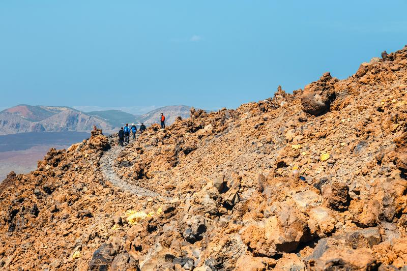 Unknown people are walking along the mountain path at the top of the el teide volcano, Spain. Tenerife, Spain, June 07, 2015: unknown people are walking along stock photos