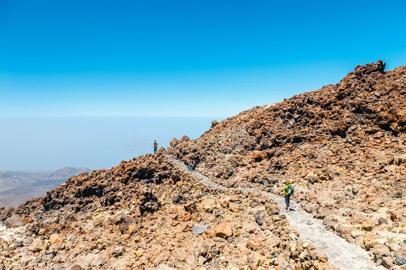 Unknown people are walking along the mountain path at the top of the el teide volcano, Spain. Tenerife, Spain, June 07, 2015: unknown people are walking along royalty free stock photography