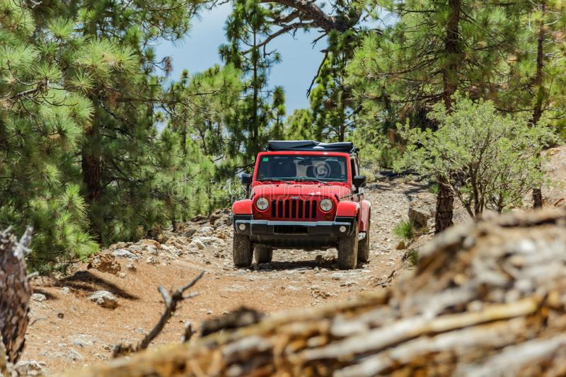 Tenerife, Spain - September 02, 2016: Jeep on a narrow rocky mountain forest road blocked by a fallen old dry pine tree. The stock images