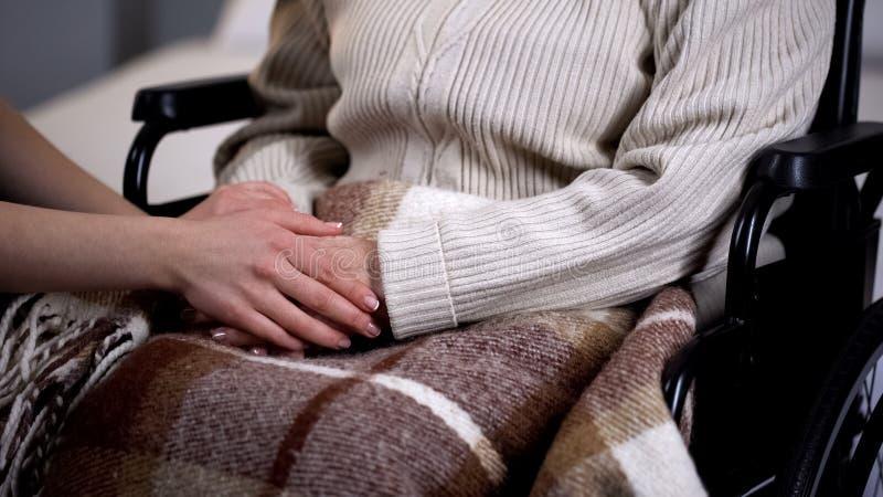 Tenersi per mano della femmina anziana handicappata, relazioni di famiglia, supporto di signora fotografie stock