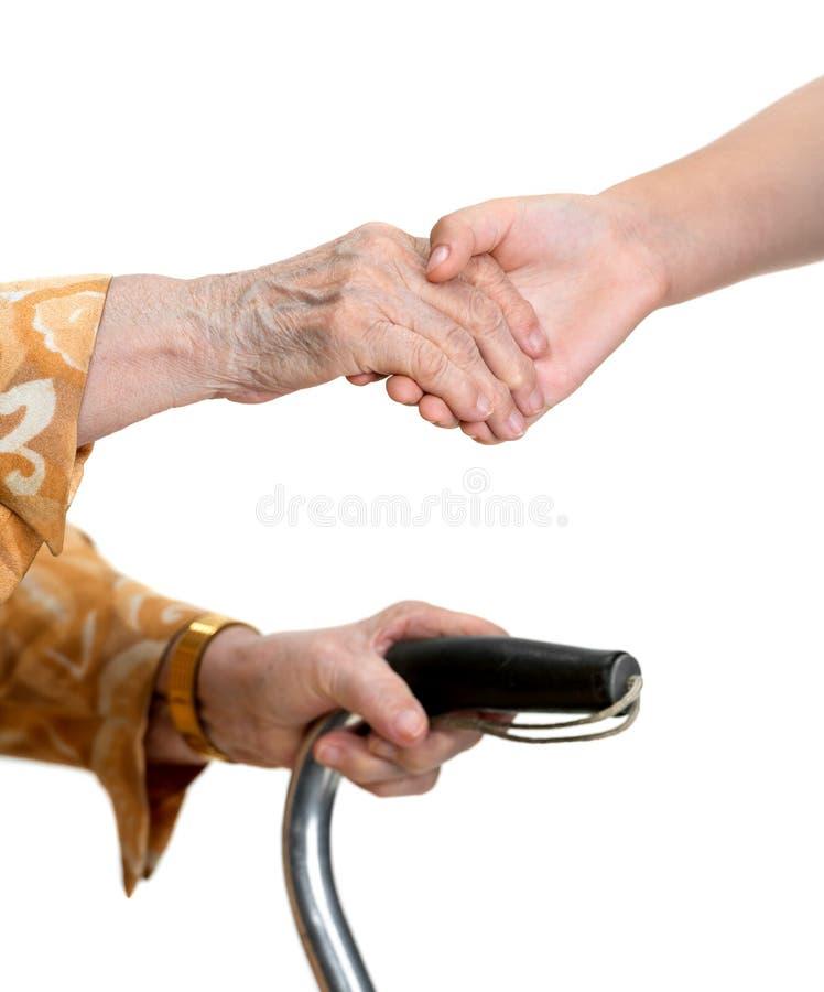 Tenersi per mano della ragazza e della donna anziana immagini stock