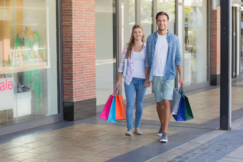 Tenersi per mano di camminata delle coppie felici immagini stock libere da diritti