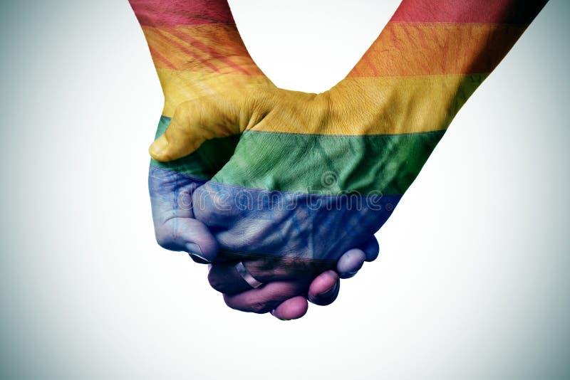 Tenersi per mano gay delle coppie, modellato come la bandiera dell'arcobaleno fotografia stock