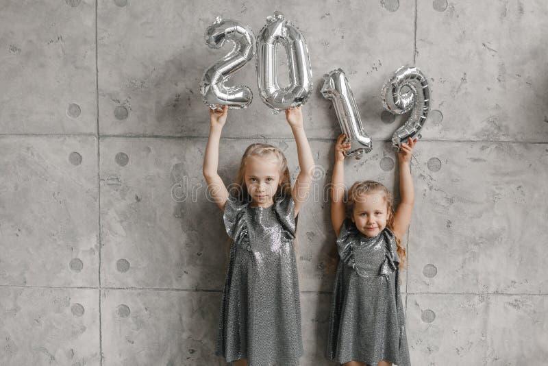 Tenersi per mano i palloni del nuovo anno, Numero 2019 Due bambine di sorriso contro il fondo grigio della parete Tempo di natale immagini stock
