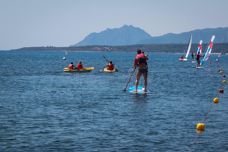 Tenez l'homme Paddleboarding de surfer à bord parmi des canoës et la victoire images stock