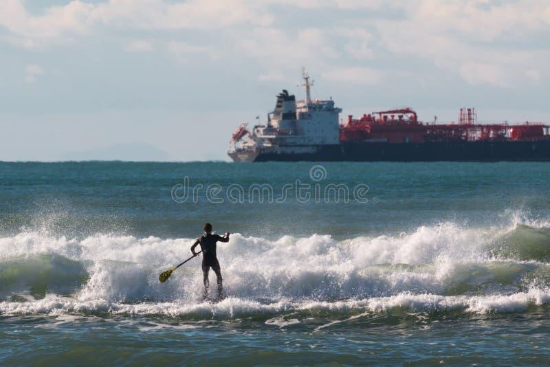 Tenez le panneau de palette, homme paddleboarding images libres de droits