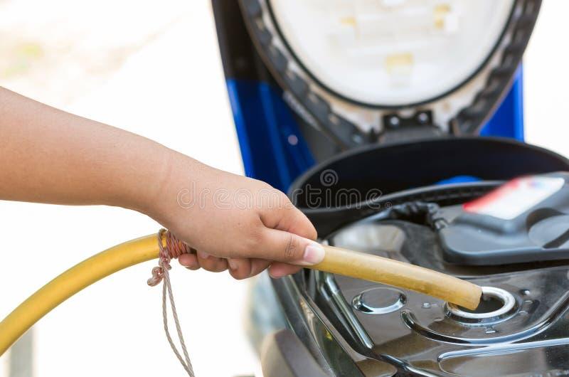Tenez le tube en caoutchouc traditionnel pour ajouter le carburant dans la moto photo stock