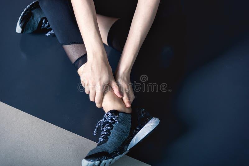 Tenga calambre del tobillo en el entrenamiento del ejercicio de la aptitud en gimnasio imagenes de archivo