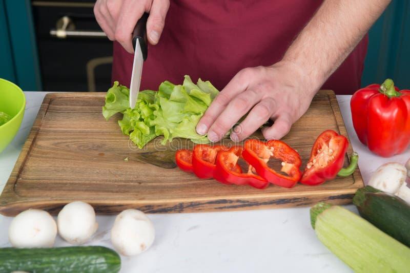 Tenga cuidado con el cuchillo El cocinero enseña a cómo rápidamente las verduras de la tajada La comida de la tajada con segurida imagen de archivo