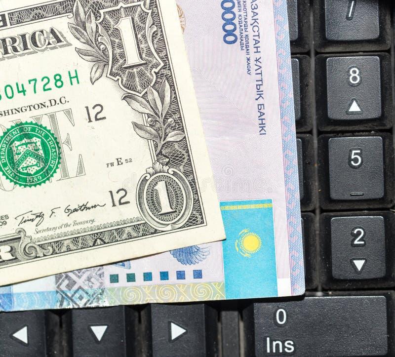 Tenge kazakh et dollars sur un clavier d'ordinateur portable photographie stock