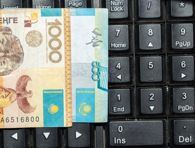 Tenge kazakh sur le clavier d'ordinateur portable photographie stock libre de droits