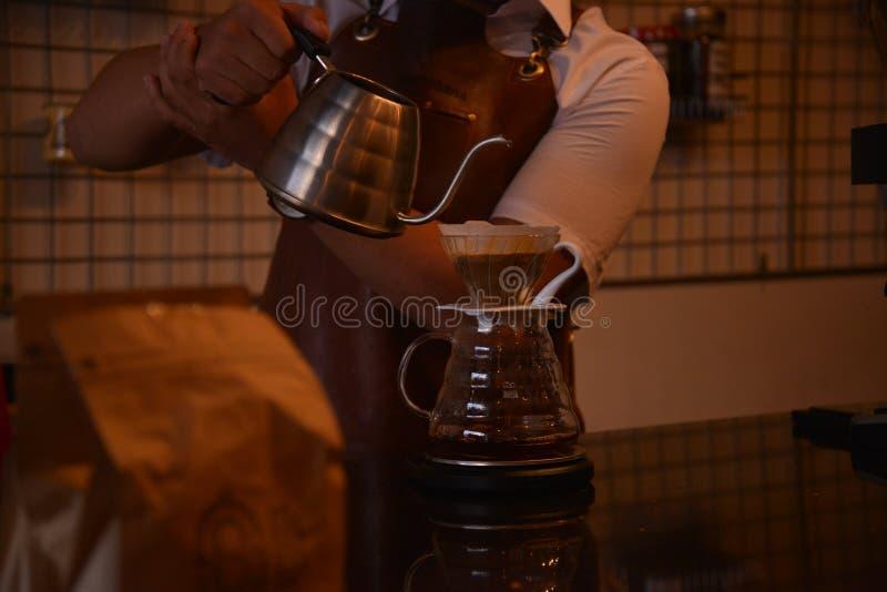 TENGGARONG, INDONESIË - MEI 2017: De knappe koffie die van de baristakoffie kop en het maken van het Concept van de koffiedienst  royalty-vrije stock afbeeldingen