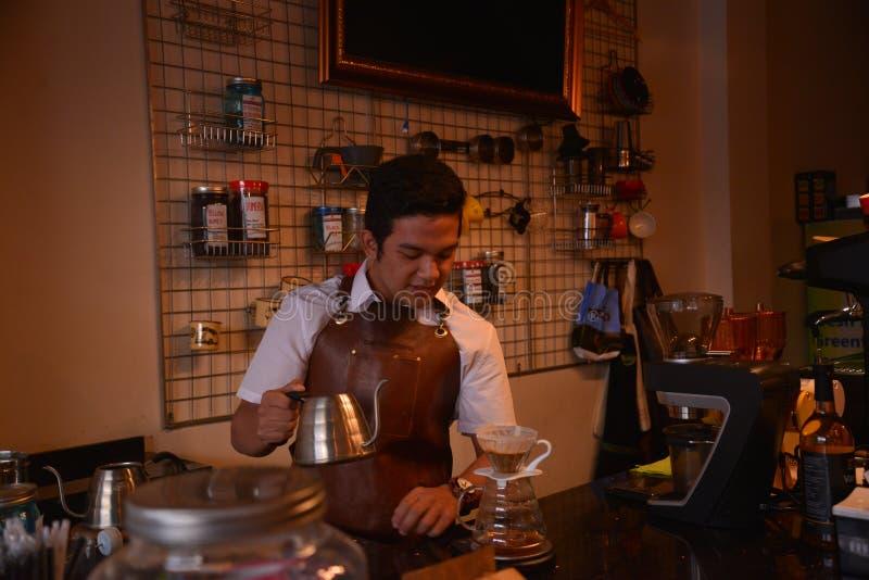 TENGGARONG, INDONESIË - MEI 2017: De knappe koffie die van de baristakoffie kop en het maken van het Concept van de koffiedienst  stock foto