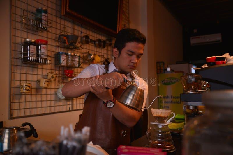 TENGGARONG, INDONESIË - MEI 2017: De knappe koffie die van de baristakoffie kop en het maken van het Concept van de koffiedienst  stock foto's