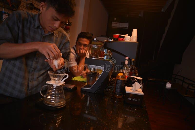 TENGGARONG INDONESIEN - MEI 2017: Stiligt baristakafékaffe som förbereder koppen och in gör av begreppet för kaffeservice för kun fotografering för bildbyråer