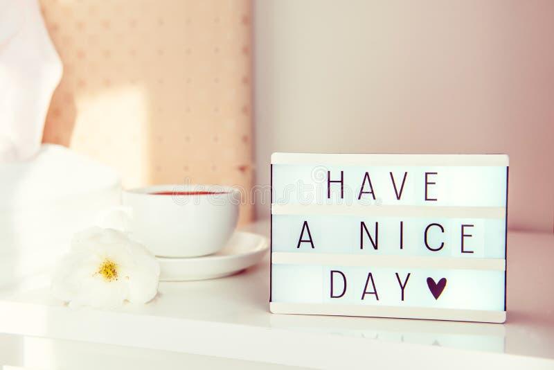 Tenha uma mensagem de texto do dia agradável na caixa leve, na xícara de café e na flor branca na tabela de cabeceira na luz do s fotografia de stock