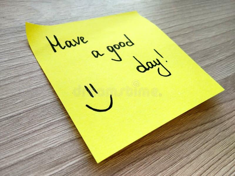 Tenha uma mensagem escrita à mão do bom dia na nota pegajosa amarela no fundo de madeira foto de stock royalty free