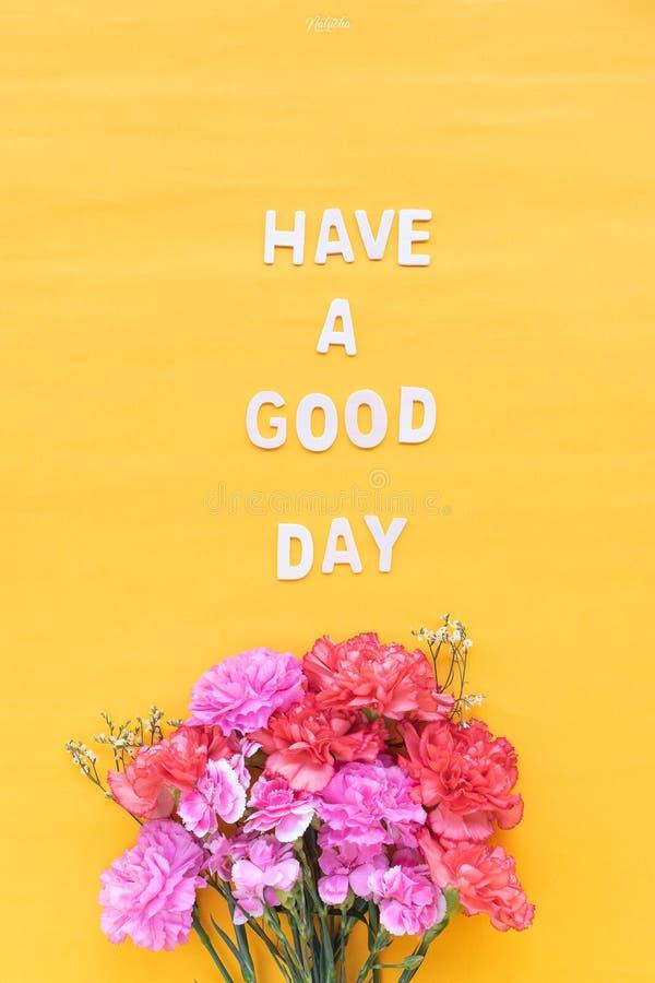 Tenha uma palavra de madeira do bom dia com os cravos das flores frescas em b foto de stock royalty free