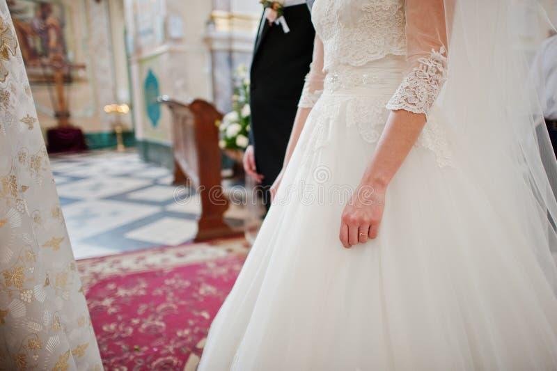 Tenir des mains des couples de mariage à la cérémonie d'église photographie stock libre de droits