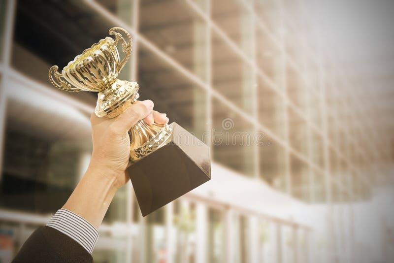 Tenir des récompenses de trophée après réussi photographie stock libre de droits