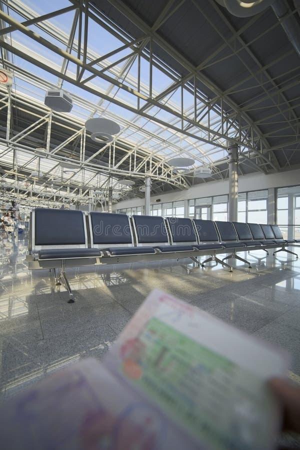 Tenir le passeport dans l'aéroport image libre de droits