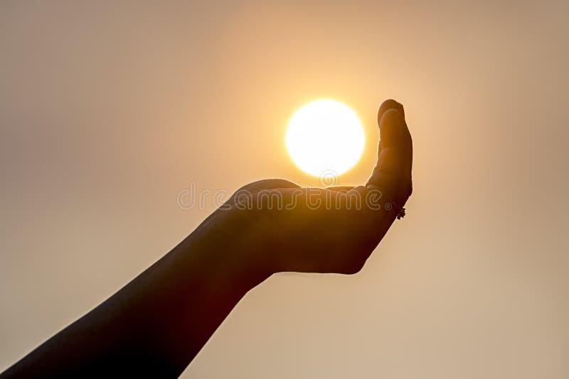 Tenir le soleil dans la paume images libres de droits