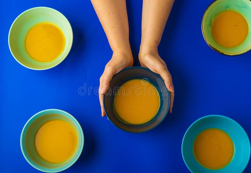 Tenir un bol de soupe à potiron images stock