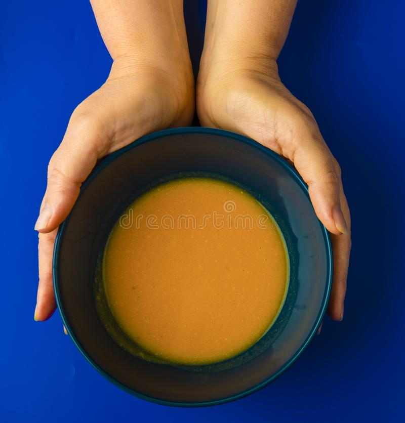 Tenir un bol de soupe à potiron photographie stock
