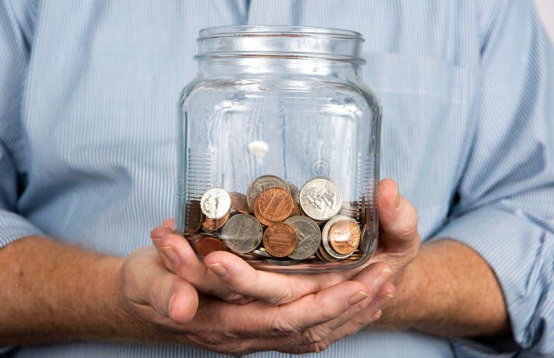 Tenir un pot d'argent de pièces de monnaie photo stock