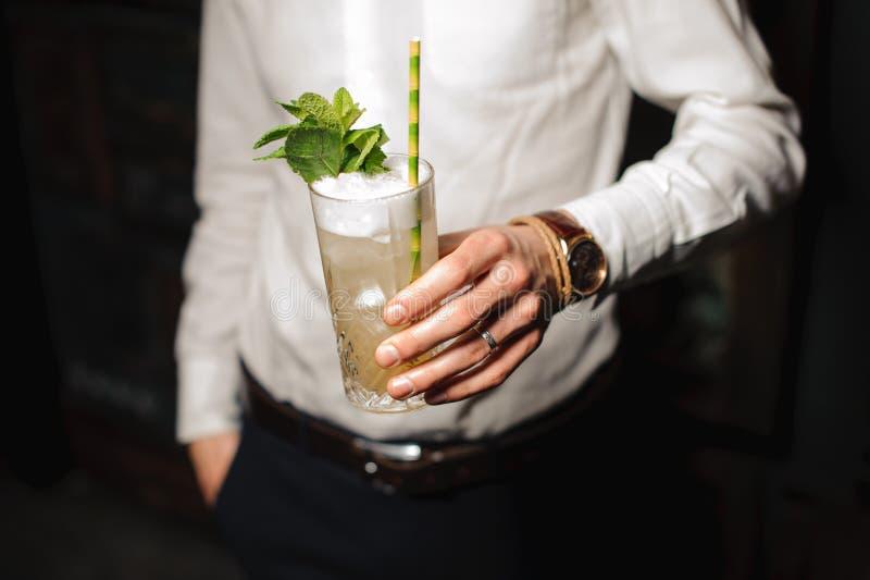 Tenir un verre de cocktail de mojito photographie stock